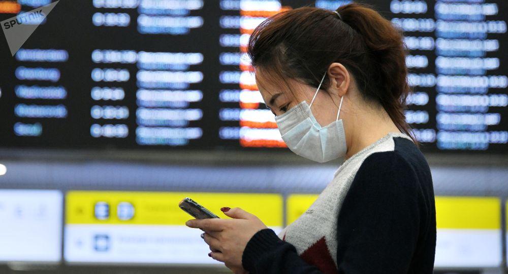 Медициналык маска кийген аэропорттогу кыз