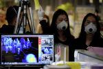 Пассажиры в масках для предотвращения заражения коронавирусом проходят мимо тепловизионной камеры по прибытии в международный аэропорт Инчхон в Инчхоне. Южная Корея, 3 января 2020 года