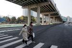 Люди надевают маски, пересекая пустую главную улицу в Чанша, провинция Хунань. Китай, 29 января 2020 года