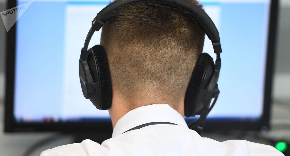 Мужчина за компьютером с наушниками. Архивное фото