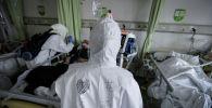 Медицинские работники в защитных костюмах обслуживают новых пациентов с коронавирусом в изолированном отделении больницы в Ухане. Провинция Хубэй, Китай, 6 февраля 2020 года