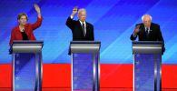 Кандидаты в президенты от Демократической партии сенатор Элизабет Уоррен, штат Массачусетс, слева, бывший вице-президент Джо Байден (в центре) и сенатор Берни Сандерс во время первичных дебатов на выборах президента Демократической партии. 7 февраль, 2020 в Манчестере