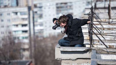 Мужчина фотографирует находясь на крыше дома. Архивное фото