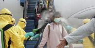 Индонезийцев, прибывших из Уханя, опрыскивают антисептиком в аэропорту Ханг-Надим.