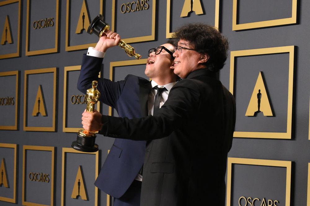 Сценарист Хан Джин-вон и режиссер фильма Паразиты Пон Чжун Хо со статуэтками премии Оскар