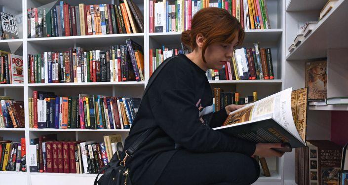 Посетительница возле полок с книгами. Архивное фото