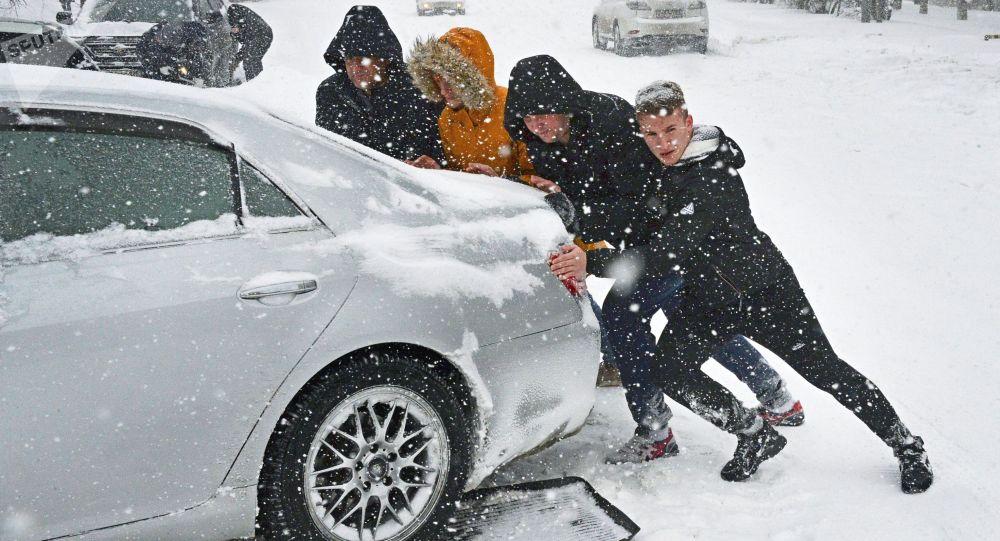 Люди толкают машину на одной из занесенных снегом улиц. Архивное фото