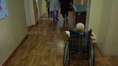 Ребенок в инвалидной коляске в детском отделении Национального центра онкологии и гематологии в Бишкеке
