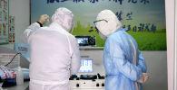 Медицинские работники в защитных костюмах осматривают оборудование. Архивное фото