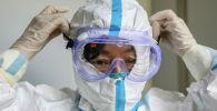 Медициналык бет кап кийген кытайлык кызматкер. Архивдик сүрөт