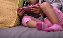 Девочка смотрит видео на телефоне. Архивное фото