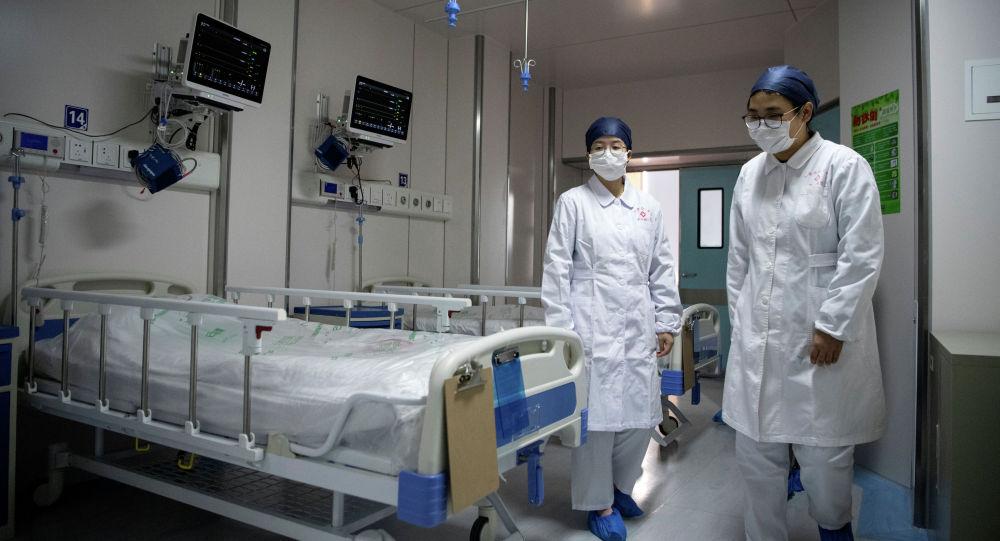 Медсестры входят в карантинную комнату где лежат пациенты зараженные коронавирусом
