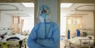 Медицинский работник в защитном костюме отдыхает в изолированном отделении больницы в Ухане. Архивное фото