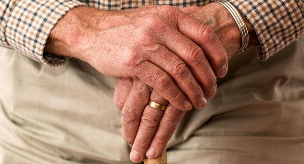 Руки пожилого мужчины держащий трость. Иллюстративное фото