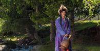 Девушка в национальном кыргызском костюме с сосудом на руках на джайлоо Кок-Жайык в ущелья Джети-Огуз
