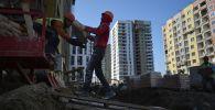 Рабочие на строительной площадке жилого комплекса. Архивное фото