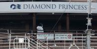 Рабочий в защитном снаряжении идет на круизном корабле Diamond Princess, пострадавшем от коронавируса, в порту Иокогама, к югу от Токио. Япония, 20 февраля 2020 года