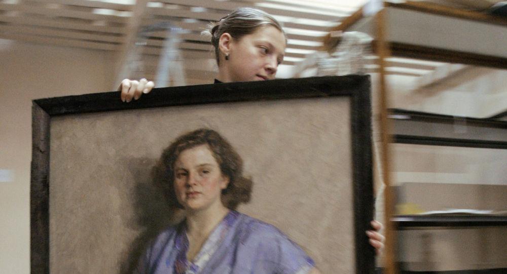 Работник музея переносит картины. Архивное фото