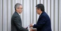 Вице-премьер-министр Эркин Асрандиев обменивается рукопожатием с Главой государства