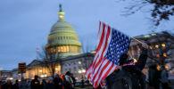 Протестующий с национальным флагом США  возле здания Капитолия в Вашингтоне