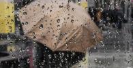 Девушка стоит с зонтом во время дождя. Архивное фото