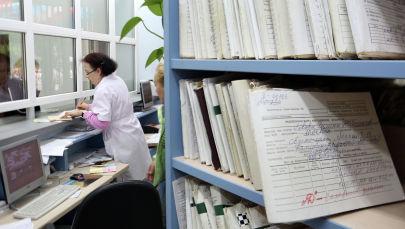 Медицинский работник выдает медицинскую карту пациенту в регистратуре Светлогорской центральной районной поликлинике, открытой вновь после капитального ремонта.