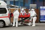 Медицинские работники в защитных костюмах доставляют зараженного коронавирусом в больницу, Чхунчхон, Южная Корея. 22 февраля 2020 года