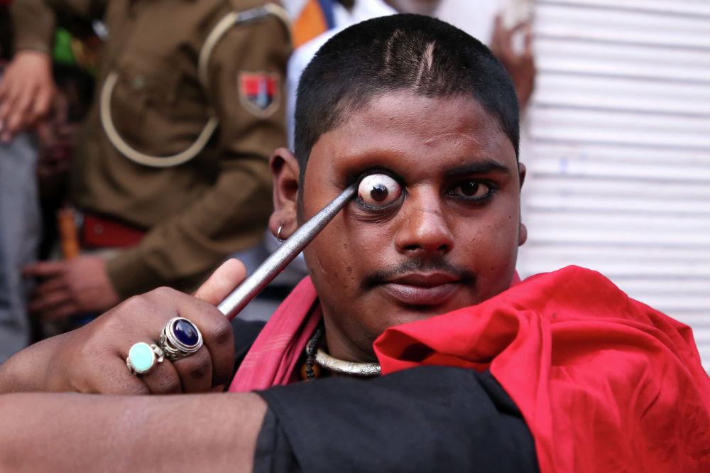 Участник ежегодного религиозного фестиваля Урс выполняет трюк в индийском штате Раджастхан. 20 февраля 2020 года
