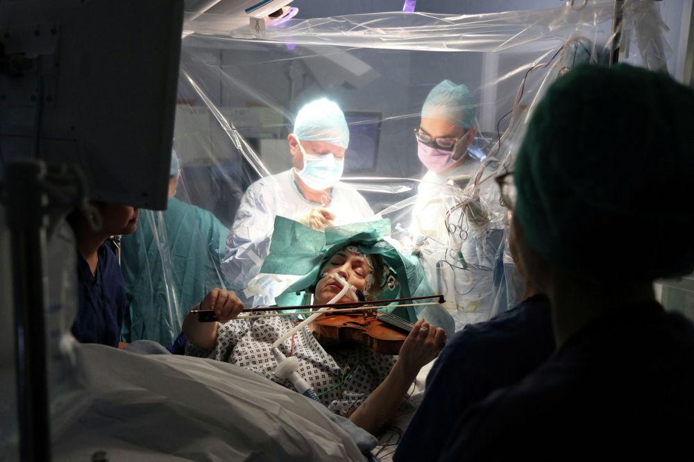 Пациентка играет на скрипке во время операции по удалению опухоли мозга в больнице Королевского колледжа в Лондоне