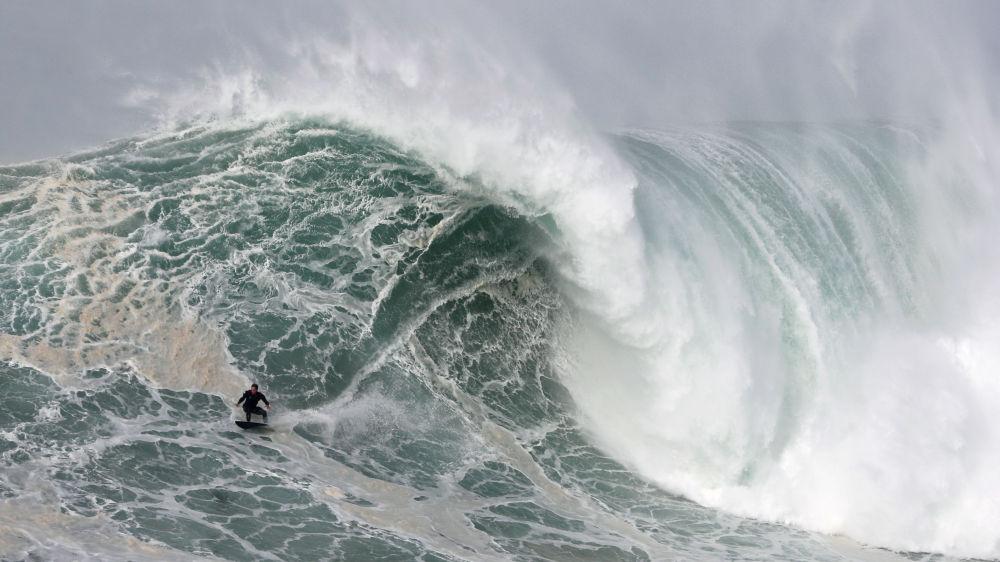 Серфингист на пляже в Назаре (Португалия)