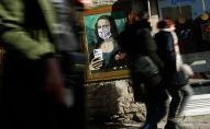 Люди проходят мимо картины на одной из улиц Барселоны, в котором изображена Мона Лиза в защитной маске.