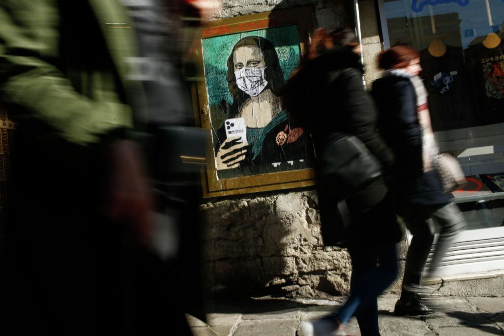 Люди в Барселоне (Испания) проходят мимо картины, на которой изображена Мона Лиза в медицинской маске.