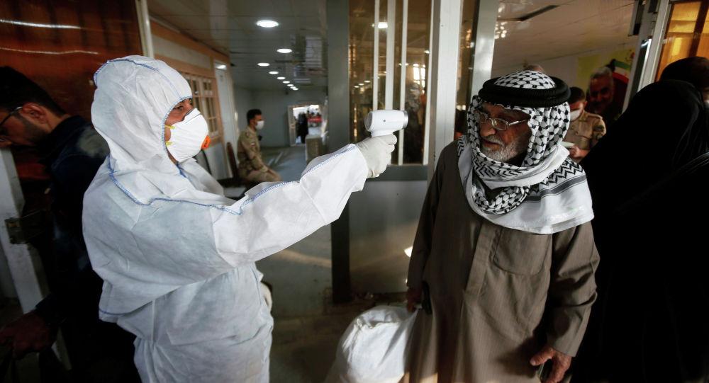 Иракский медицинский сотрудник проверяет температуру пассажира по прибытии на пограничный переход Шаламча между Ираком и Ираном, 20 февраля 2020 года