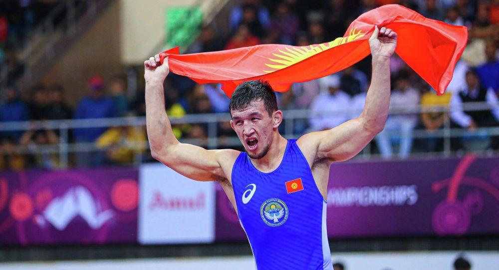 Чемпион Азии по вольной борьбе, кыргызстанец Арсалан Будажапов с флагом Кыргызстана после победы над соперником в финале чемпионата Азии