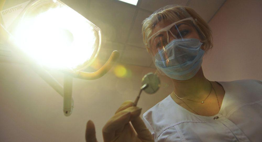 Врач-стоматолог во время приема пациента. Архивное фото