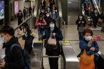 Пассажиры в защитных масках на станции метро в Гонконге.