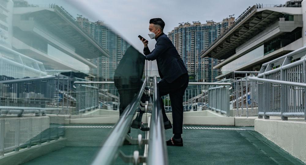 Мужчина носит лицевую маску в качестве профилактической меры против коронавируса COVID-19, когда он наблюдает за гонками в день Золотого кубка Гонконга на ипподроме Ша Тин. Архивное фото