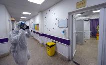 Врач в защитной маске в больнице, где проходит лечение заразившихся коронавирусом COVID-19