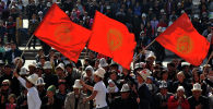 Молодые люди в белых калпаках несут флаг Кыргызстана. Архивное фото