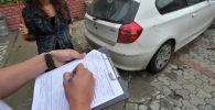 Сотрудник компании проводит осмотр страхуемого автомобиля. Архивное фото