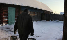 Мужчина носит воду для бани в селе. Архивное фото