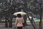 Аял колунда зонтик менен көчөдө басып жүрөт. Архив
