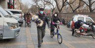 Жители Пекина идут в медицинских масках по улице.