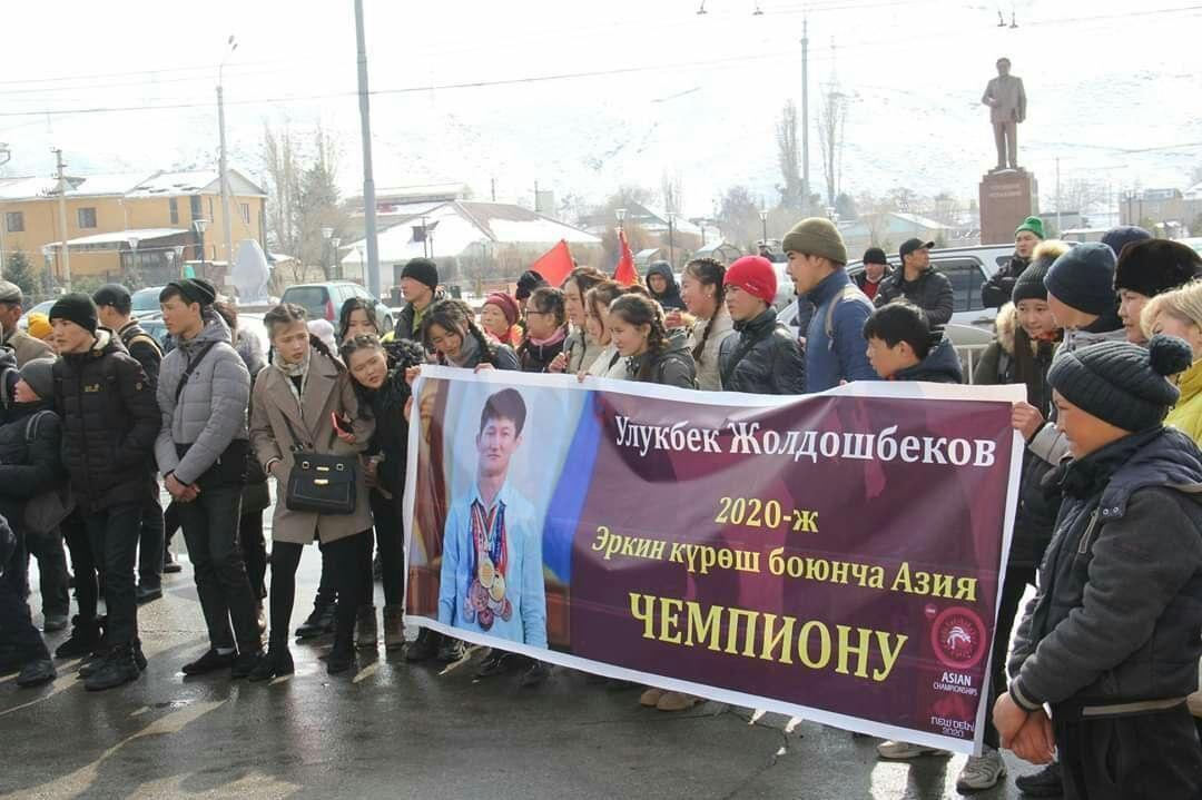 Жители города Нарын с плакатом чемпиона Азии по вольной борьбе до 61 килограмм Улукбека Жолдошбекова