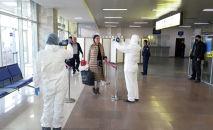 Медицинские работники в аэропорту Манас проверяют температуру пассажиров, прибывающих из других стран. Архивное фото