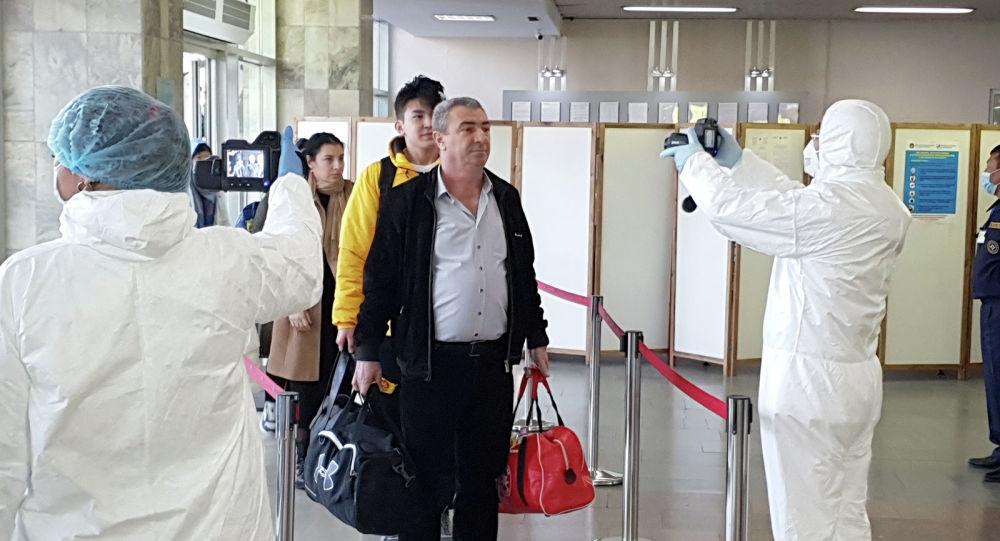 Медицинские работники в аэропорту Манас проверяют пассажиров, прибывающих из других стран
