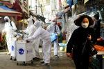 Женщина, носящая маску для предотвращения заражения коронавирусом, реагирует на то, что сотрудники дезинфекционной компании дезинфицируют традиционный рынок в Сеуле. Южная Корея, 26 февраля 2020 года
