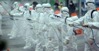 Южнокорейские солдаты, одетые в защитное снаряжение, дезинфицируют железнодорожную станцию
