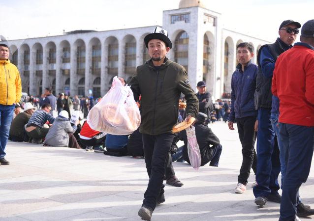 Сторонник Садыра Жапарова несет лепешки во время митинга на площади Ала-Тоо с требованием освободить политика в Бишкеке