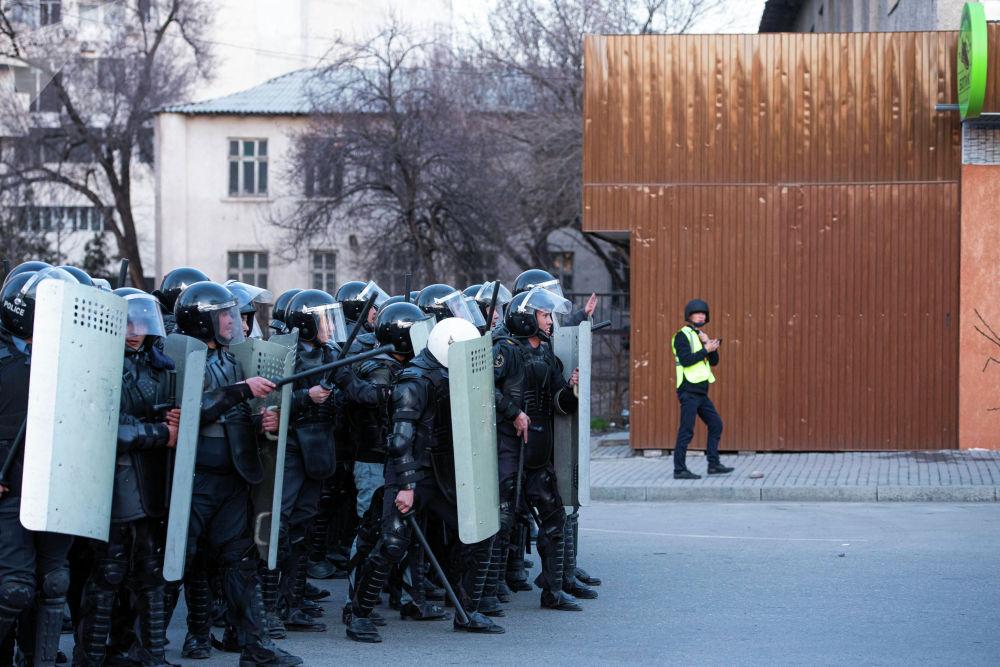 Орозбеков көчөсүндөгү милиционерлер. Арткы фондо Sputnik журналисти митингди коопсуздук кийимчен чагылдырып жүрөт.